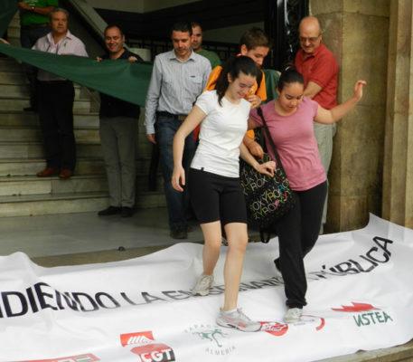Alumnos del Celia Viñas pasan por encima de la pancarta ajenos a las reivindicaciones