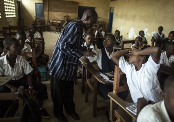 (Standing) a teacher speaks with a schoolgirl during a class at Monrovia Demonstration School in Monrovia, the capital, on the first day of the new academic year.  On 7 September 2015 in Liberia, education resumed for the new academic year following a five-week school break. Schools across the country officially reopened on 16 February, after being closed for six months due to the Ebola virus disease (EVD) outbreak. Liberia was among countries in West Africa affected by the worst outbreak of EVD in history. At the peak of transmission, in late August and early September 2014, the country recorded 300–400 new Ebola cases a week, but the situation had begun to improve towards the end of the year. The World Health Organization (WHO) declared the country free of Ebola virus transmission on 3 September 2015. No new cases were recorded over a 42-day period since the second negative test, on 22 July 2015, of the last laboratory-confirmed case. The country has entered a 90-day period of heightened surveillance. Transmission had previously been declared over on 9 May 2015, but the disease re-emerged on 29 June, and six additional cases were identified. Communities have played a central role in battling the virus, which has killed more than 11,300 people since January 2014 and has taken a toll on almost every aspect of the lives of over 9 million children living in Ebola-affected areas. Thousands of children have contracted or have been killed by the disease, and more than 16,000 of them have lost one or both parents or their primary caregiver. EVD has also disrupted essential services that were already fragile before the crisis, including critical health care and education. UNICEF remains at the forefront of a Liberia's Ebola response efforts and co-leads the water, sanitation and hygiene (WASH), psychosocial support services and social mobilization pillars of the response. Working closely with national and local governments and other partners, UNICEF supports efforts