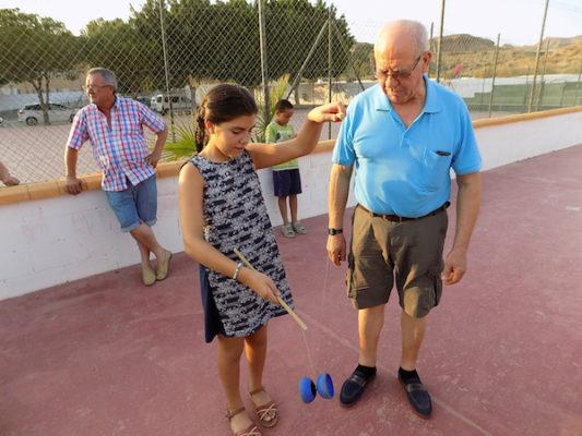 Nieta y abuelo jugando con el diábolo