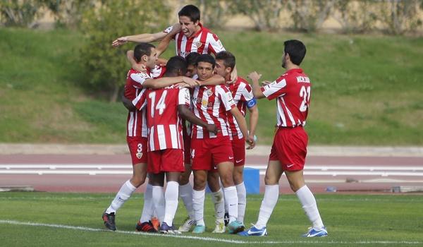 Piña de futbolistas del Almería B con varios juveniles en plan heróico