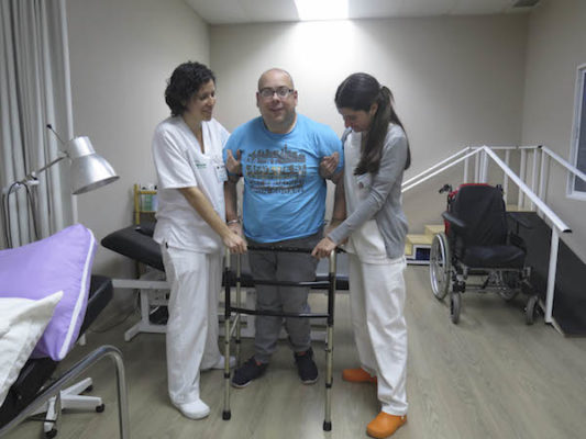 Usuario dependiente realizando actividades de fisioterapia en el centro de Verdiblanca junto a dos especialistas